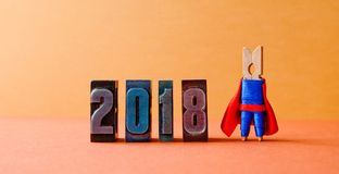 Super successful 2018 new year card. Brave superhero leader posing on vintage letterpress digits. Beautiful clothespin. Metaphor character in red blue costume Stock Images