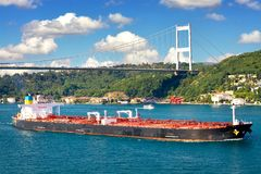 Super Tanker. A large tanker ship sails under the Bosporus Bridge Stock Photo