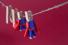 Super team leadership concept photo with clothespin superheroes in blue suit and red cape. Big small powerful heroes Royalty Free Stock Image