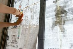 Super typhoon Mangkhut heads for China and a lady gluing newspaper to the glass windows to reinforce them Royalty Free Stock Photos
