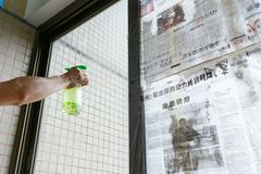 Super typhoon Mangkhut heads for China and a lady gluing newspaper to the glass windows to reinforce them Royalty Free Stock Images