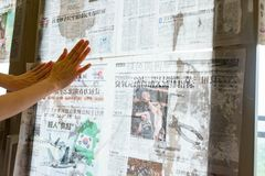 Super typhoon Mangkhut heads for China and a lady gluing newspaper to the glass windows to reinforce them Stock Image