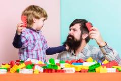 Super vader de bouwhuis met kleurrijke aannemer Gelukkige familievrije tijd Kindontwikkeling kleine jongen met papa stock foto