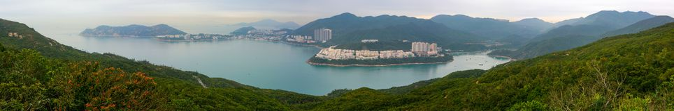Super wide panorama of Tai Tam Bay and Red Hill in Hong Kong, as seen from Dragon`s Back hiking trail royalty free stock images