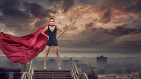 Super woman with red cape. Portrait of young hero woman with super person red cape royalty free stock image