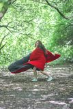 Super woman. girl in a red cloak. Among the forest. jumping that would fly up stock photography
