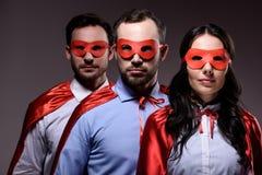 super zakenlui in maskers en kaap die camera bekijken stock foto