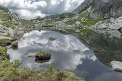 Superb alpine lake among white summer clouds. In Retezat, Romania Royalty Free Stock Photography