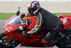Superbike racing on track. Superbike rider leaning into a corner at high speed, racing on a race track stock photo