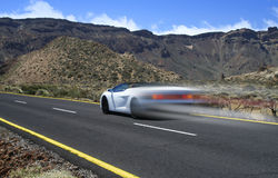 Supercar in desert. White sportscar zooming on desert asphalt road royalty free stock images