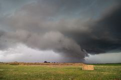 A supercell storm with a low shelf cloud hangs ominously over farmland in Nebraska. Stock Image