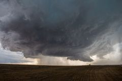 A supercell thunderstorm develops a wall cloud and begins to rotate over the plains of eastern Colorado. A supercell thunderstorm develops a wall cloud and stock images
