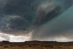 Supercell thunderstorm with dramatic clouds and hail. Supercell thunderstorm with dark, dramatic storm clouds and eerie green hail core approaching Tucumcari stock photo