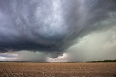 A supercell thunderstorm dumps heavy rain and hail over a field. A supercell thunderstorm dumps heavy rain and hail over an empty field stock images
