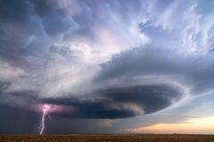 Supercell thunderstorm with lightning bolt and dark storm clouds