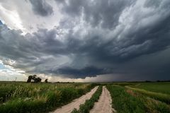 A supercell thunderstorm looms in the sky over a dirt road in farmland. A supercell thunderstorm looms in the sky over a dirt road in farm country royalty free stock images