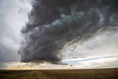 A supercell thunderstorm towers over the great plains landscape. A supercell thunderstorm towers over the landscape of the Great Plains stock image