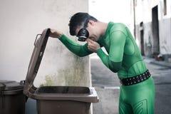 Supereroe che apre un bidone della spazzatura Fotografia Stock Libera da Diritti