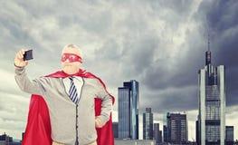 Supereroe che prende selfie davanti alla città scura Fotografie Stock