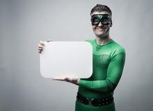 Supereroe che tiene un segno in bianco immagine stock