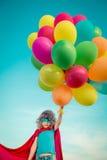 Supereroe con i palloni del giocattolo nel giacimento di primavera Immagini Stock