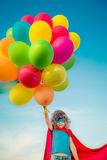Supereroe con i palloni del giocattolo nel giacimento di primavera Immagine Stock Libera da Diritti