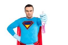 supereroe maschio in guanti di gomma che tengono la bottiglia dello spruzzo con il detersivo e che esaminano macchina fotografica fotografia stock