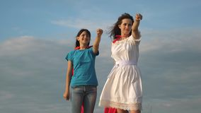 Supereroi di lavoro di squadra due ragazze in mantelli rossi dei supereroi stanno contro un cielo blu, il vento gonfia un mantell video d archivio