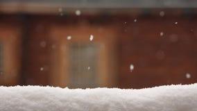 Superfície coberto de neve para a colocação do produto Parede de madeira borrada da casa com a janela no fundo Queda de neve pesa filme