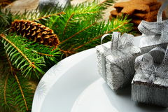 Superfície de madeira dos pinhos dos presentes da prata da placa do Natal do close up Fotos de Stock Royalty Free