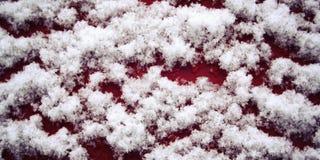 Superfície de madeira vermelha coberta com a neve Fim acima imagens de stock royalty free