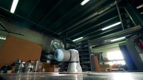 Superfície de metal com um robô industrial movente unido a ele filme