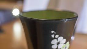 Superfície do copo preto com as flores brancas e verdes Imagem de Stock