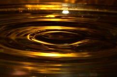 Superfície dourada da água, respingo da água Imagem de Stock Royalty Free