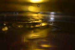 Superfície dourada da água, respingo da água Imagens de Stock Royalty Free