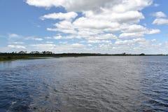 Superfície Rippled da água e céu azul nebuloso Imagens de Stock