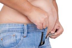 Superficie abdominal de la mujer gorda en el fondo blanco Imagen de archivo libre de regalías