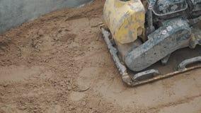 Superficie de compresión de trabajo a cámara lenta de la arena del compresor amarillo de la placa de la gasolina metrajes