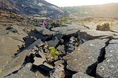 Superficie de exploración del turista femenino joven del cráter del volcán de Kilauea Iki con la roca de la lava que desmenuza en Fotos de archivo libres de regalías