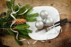 Superficie de madera de los pinos de las chucherías de la plata de la placa de la Navidad Imágenes de archivo libres de regalías