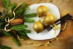 Superficie de madera de los pinos de oro de las chucherías de la placa de la Navidad Foto de archivo