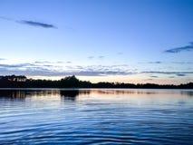 Superficie del lago alla sera in Lettonia, Europa orientale Paesaggio con acqua e la foresta fotografia stock libera da diritti