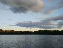 Superficie del lago en la tarde en Letonia, Europa del este Paisaje con agua y el bosque Imagen de archivo libre de regalías