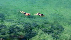 Superficie del mar de dos turistas que bucea