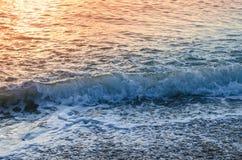 Superficie del mare, onda e luce di tramonto fotografia stock libera da diritti