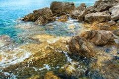 Superficie del mare, rocce sulla riva Fotografia Stock