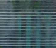 Superficie del policarbonato con gli oggetti verdi dietro fotografia stock libera da diritti