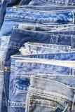 Superficie dell'abbigliamento impilata denim delle blue jeans Immagini Stock
