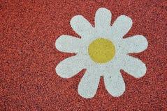 Superficie di gomma del campo da giuoco con il fiore bianco Fotografia Stock