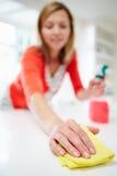 Superficie di pulizia della donna in cucina Fotografia Stock